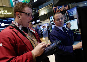 Photo -  Trader Ryan Falvey, left, and specialist Jason Notter, work Tuesday on the floor of the New York Stock Exchange.  AP Photo  <strong>Richard Drew -   </strong>