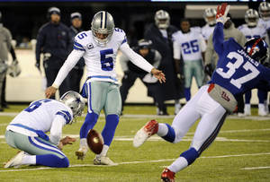 Photo - Dallas Cowboys kicker Dan Bailey (5), with Chris Jones holding, kicks a game-winning field goal against the New York Giants during the second half of an NFL football game, Sunday, Nov. 24, 2013, in East Rutherford, N.J. The Cowboys won 24-21. (AP Photo/Bill Kostroun)