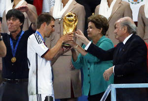 Photo - Germany's team captain Philipp Lahm, second left, receives the World Cup trophy by Brazil's President Dilma Rousseff and FIFA President Sepp Blatter, right, during the World Cup final soccer match between Germany and Argentina at the Maracana Stadium in Rio de Janeiro, Brazil, Sunday, July 13, 2014. (AP Photo/Frank Augstein)