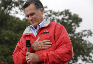 photo -   Republican presidential candidate, former Massachusetts Gov. Mitt Romney puts his hand on his heart during a moment of silence for the embassy officials killed in Libya, as he campaigns in the rain at Lake Erie College in Painesville, Ohio, Friday, Sept. 14, 2012. (AP Photo/Charles Dharapak)