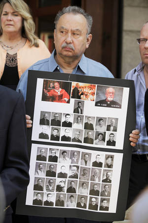Photo - Arthur Budzinaki  holds poster of the 45 priests named on the archdiocese's website as having substantiated allegations of sexually abusing at least one minor as the group addressed the media regarding release of Milwaukee priest sex abuse files the outside - the U.S. Federal Courthouse in Milwaukee on Monday, July 1, 2013.  About 6,000 pages of documents were released by Archdiocese of Milwaukee  Monday as part of a deal reached in federal bankruptcy court with clergy sex abuse victims suing it for fraud.  Photo by(AP Photo/Milwaukee Journal-Sentinel, Mike De Sisti)