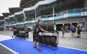 Photo - A Red Bull pit staff member pushes sets of tires in the paddock ahead of the Malaysian Formula One Grand Prix at Sepang International Circuit in Sepang, Malaysia, Thursday, March 27, 2014. (AP Photo/Peter Lim)