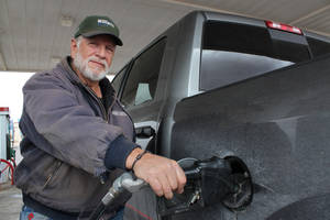 Photo - Larry Maestas, a Sandoval County rancher and oil and natural gas worker, fills up his pickup Monday in Bernalillo, N.M. Maestas drives as much as 200 miles a day and spent $18,000 on fuel last year. AP Photo