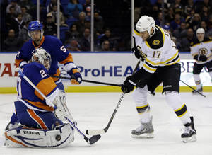 photo - New York Islanders goalie Evgeni Nabokov (20) blocks a shot by Boston Bruins left wing Milan Lucic (17) in the first period of their NHL hockey game at Nassau Coliseum in Uniondale, N.Y., Tuesday, Feb. 26, 2013. (AP Photo/Kathy Willens)