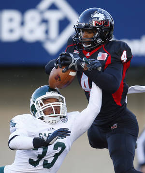 Photo - Northern Illinois wide receiver Da'Ron Brown (4) catches a touchdown pass off the head of Eastern Michigan defensive back Quan Pace (33) during the second half of an NCAA college football game, Saturday, Oct. 26, 2013, in DeKalb, Ill. (AP Photo/Jeff Haynes)