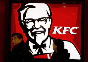 Photo - A Chinese couple walk past a KFC restaurant at a shopping mall in Beijing Monday, Feb. 25, 2013. KFC launched a campaign Monday to rebuild its battered brand in China, promising tighter quality control after a scandal over misuse of drugs by its poultry suppliers. (AP Photo/Andy Wong)