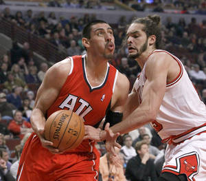 Photo - Atlanta Hawks forward Gustavo Ayon (14) looks to the basket as Chicago Bulls center Joakim Noah (13) defends during the first half of an NBA basketball game Tuesday, Feb. 11, 2014, in Chicago. (AP Photo/Charles Rex Arbogast)