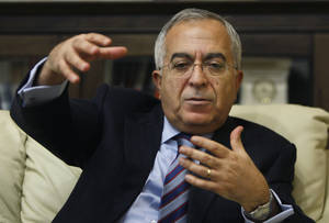 Photo - Palestinian Prime Minister Salam Fayyad gestures during an interview with The Associated Press in the West Bank city of Ramallah, Sunday, Jan. 6, 2013. Fayyad is blaming Arab countries that haven't delivered promised financial aid for an escalating financial crisis in the Palestinian territories. In an interview Sunday Fayyad said that the cash crunch is pushing an additional 25 percent of the Palestinian population, or 1 million people, into poverty. (AP Photo/Majdi Mohammed)