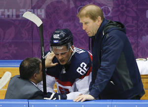 Photo - Slovakia forward Tomas Kopecky is checked by a trainer in the first period of a men's ice hockey game against Slovenia at the 2014 Winter Olympics, Saturday, Feb. 15, 2014, in Sochi, Russia. (AP Photo/Mark Humphrey)