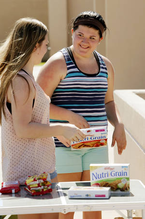 Photo - Jordan Eshbaugh, 14, right, collects items for a care package for her  father's former National Guard unit.  PHOTO BY STEVE SISNEY, THE OKLAHOMAN