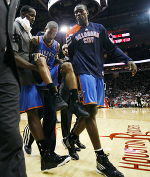 photo - Oklahoma City Thunder guard Eric Maynor (6) is carried off the court by teammates after suffering an injury on a drive to the basket during the fourth quarter of an NBA basketball game against the Houston Rockets, Saturday, Jan. 7, 2012, in Houston. The Thunder won 98-95. (AP Photo/Eric Kayne) ORG XMIT: TXELK112