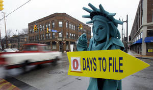 Photo -   FILE-In this Monday, April 18, 2011, file photo, Max Martinez, dressed as the Statue of Liberty, tries to alert motorists on the final day to file taxes. A typical middle-income family making $40,000 to $64,000 a year could see its taxes go up by $2,000 in 2013 if lawmakers fail to renew a lengthy roster of tax cuts set to expire at the end of 2012, according to a new report Monday, Oct. 1, 2012. Taxpayers across the income spectrum would be hit with large tax hikes, the Tax Policy Center said in its study, with households in the top 1 percent income range seeing an average tax increase of more than $120,000, while a family making between $110,000 to $140,000 could see a tax hike in the $6,000 range. (AP Photo/Tony Dejak, File)