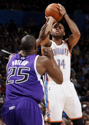 Photo - Oklahoma City's Daequan Cook (14) shoots over Sacramento's Travis Outlaw (25) during the NBA basketball game between the Oklahoma City Thunder and the Sacramento Kings at Chesapeake Energy Arena in Oklahoma City, Friday, April 13, 2012. Photo by Nate Billings, The Oklahoman