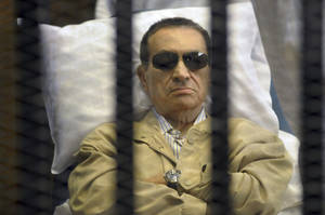 Photo -   Egypt's ex-President Hosni Mubarak lays on a gurney inside a barred cage in the police academy courthouse in Cairo, Egypt, Saturday, June 2, 2012. Mubarak was sentenced to life in prison Saturday for his role in the killing of protesters during last year's revolution that forced him from power, a verdict that caps a stunning fall from grace for a man who ruled the country as his personal fiefdom for nearly three decades.(AP Photo)