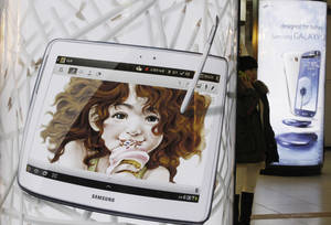 photo - A woman uses her smartphone between a billboard of Samsung Electronics' Galaxy S III and Galaxy Note 10.1, left, at a subway station in Seoul, South Korea, Friday, Jan. 25, 2013. Samsung Electronics Co. said quarterly profit soared 76 percent, boosted by the popularity of its Galaxy smartphones, which outsold the iPhone for a fourth straight quarter. But the company said Friday it expects earnings to decline during the current quarter because of seasonally low demand for consumer electronics. (AP Photo/Ahn Young-joon)