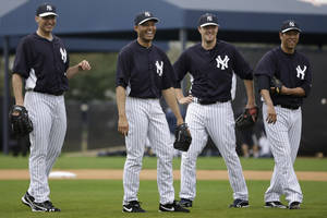photo - New York Yankees' Andy Pettitte, from left, Mariano Rivera, Phil Hughes and Hiroki Kuroda, of Japan, laugh during a workout at baseball spring training, Wednesday, Feb. 13, 2013, in Tampa, Fla. (AP Photo/Matt Slocum)