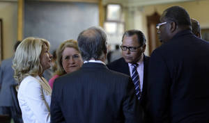 Photo - Sen. Wendy Davis, D-FortWorth, left, talks with fellow senators in the Senate Chambers, Thursday, July 11, 2013, in Austin, Texas.  A Senate committee on Thursday pushed through new abortion restrictions, setting up a Senate vote before the weekend to send it to Gov. Rick Perry. The bill would require doctors to have admitting privileges at nearby hospitals, only allow abortions in surgical centers, dictate when abortion pills are taken and ban abortions after 20 weeks. (AP Photo/Eric Gay)