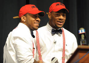 photo - Grayson High School football player Robert Nkemdiche, right, the nation's top recruit, is congratulated by his brother Denzel during Robert Nkemdiche's announcement to play college football for Ole Miss, at a Grayson, Ga., signing ceremony Wednesday Feb. 6, 2013. Denzel Nkemdiche also plays for the Rebels. (AP Photo/David Tulis)