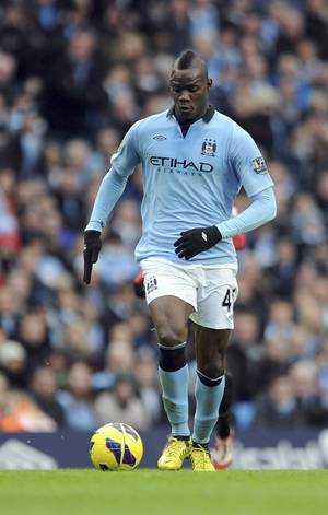 photo - FILE - This Dec. 9, 2012 file photo shows Manchester City&#039;s Mario Balotelli during a Premier League soccer match against Manchester United at the Etihad Stadium in Manchester, England. AC Milan says Tuesday, Jan. 29, 2013 that it has reached an agreement with Manchester City to sign Mario Balotelli and the Italy striker will undergo a medical on Wednesday. Balotelli is then expected to sign a four-and-a-half year deal with Milan, until 2017.  (AP Photo/Clint Hughes, files)