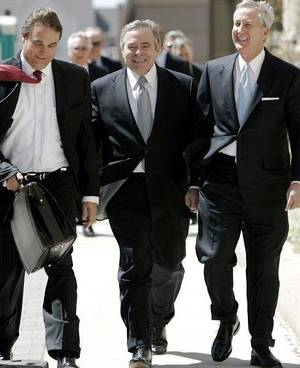 Photo - Former Senate leader Mike Morgan, center, walks to his arraignment Wednesday with his attorneys David Ogle, left, and Hal Ellis.  <strong>John Clanton - The Oklahoman</strong>