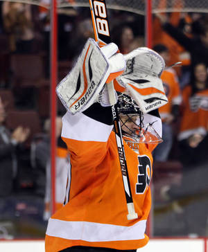 photo - Philadelphia Flyers goalie Ilya Bryzgalov celebrates after the team&#039;s 4-1 victory over the Washington Capitals in an NHL hockey game on Wednesday, Feb 27, 2013, in Philadelphia. (AP Photo/Tom Mihalek)