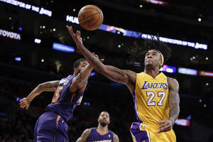 Photo - Los Angeles Lakers center Jordan Hill, right, is fouled by Phoenix Suns forward Marcus Morris during the first half of an NBA basketball game in Los Angeles, Tuesday, Dec. 10, 2013. (AP Photo/Chris Carlson)