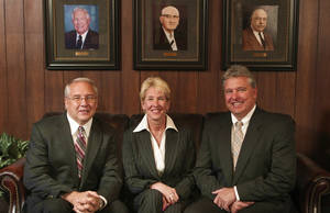 photo - Siblings and co-owners of Yukon National Bank, Randy Wright, Carolyn Henthorn and Ray Wright sit in front of portraits of their ancestors who earlier ran the bank. Randy Wright is president and CEO of the bank. Henthorn is an executive vice president.