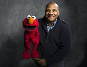 "Photo -   FILE - In this Jan. 24, 2011 file photo, Elmo puppeteer Kevin Clash poses with the ""Sesame Street"" muppet in the Fender Music Lodge during the 2011 Sundance Film Festival in Park City, Utah. Sesame Workshop says Elmo puppeteer Kevin Clash has resigned from ""Sesame Street"" in the wake of allegations that he had sex with an under-aged youth. Last week a man accused Clash of having sex with him when he was a teenage boy, a charge Clash denied. A day later, the man recanted his charge. A lawsuit by a second accuser was filed Tuesday, Nov. 20, according to attorney Cecil Singleton. (AP Photo/Victoria Will, File)"