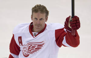 Photo - Former Ottawa Senators captain, Detroit Red Wings right wing Daniel Alfredsson acknowldges the crowd prior to the start of NHL hockey action Sunday Dec.  1, 2013 in Ottawa, Ont. The game was Alfredsson's first in Ottawa since being traded to the Red Wings. (AP Photo/The Canadian Press, Adrian Wyld)