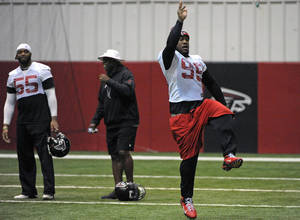 photo - Atlanta Falcons defensive tackle Jonathan Babineaux (95) leaps past secondary coach Tim Lewis and defensive end John Abraham during drills at the NFL football team's headquarters in Flowery Branch, Ga., Wednesday, Jan. 16, 2013. Atlanta is scheduled to face the San Francisco 49ers in the NFC Championship football game on Sunday. (AP Photo/David Tulis)