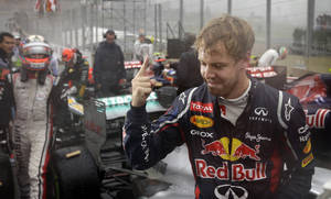 photo -   Red Bull driver Sebastian Vettel of Germany celebrates after the Formula One Brazilian Grand Prix at the Interlagos race track in Sao Paulo, Brazil, Sunday, Nov. 25, 2012. Vettel overcame a first-lap crash to clinch his third straight Formula One championship title on Sunday, finishing sixth in an incident-filled Brazilian Grand Prix won by Jenson Button under pouring rain.(AP Photo/Ricardo Mazalan)