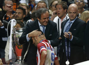 Photo - Atletico's David Villa, is patted on the head by UEFA president Michel Platini, after receiving his runner up medal,  at the end of the Champions League final soccer match between Atletico Madrid and Real Madrid, at the Luz stadium, in Lisbon, Portugal, Saturday, May 24, 2014. (AP Photo/Daniel Ochoa de Olza)