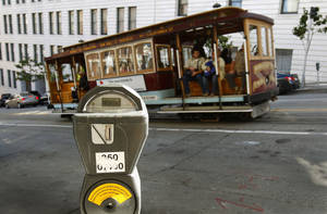 Photo - FILE - In this Oct. 27, 2009 file photo, a cable car passes a parking meter near San Francisco's financial district. San Francisco City Attorney Dennis Herrera on Monday, June 23, 2014 issued a cease-and-desist demand to a mobile app called Monkey Parking, which allows people to auction off public parking spaces that they're using to other nearby drivers. (AP Photo/Ben Margot, File)