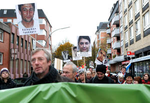 Photo -   Demonstrators march with posters showing victims of a far-right terror group in Hamburg, northern Germany, Sunday Nov. 4, 2012. Anti-racism campaigners are staging vigils across Germany to commemorate the victims of a far-right terror group whose existence came to light a year ago. Organizers called memorial events in two dozen cities Sunday to remember the victims of the National Socialist Underground. The group is suspected of killing at least nine men and a police officer during a seven-year murder spree that began in 2000. (AP Photo/dapd/Sven Klein)