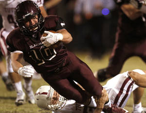 Photo - Blanchard's Braden Stringer is brought down by Tuttle's Tanner Brannon during the high school football game between Blanchard and Tuttle in Blanchard,Okla.,  Friday, Nov. 8, 2013. Photo by Sarah Phipps, The Oklahoman