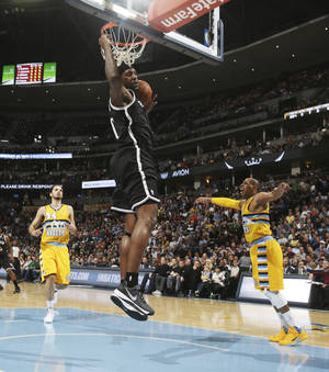 Photo - Brooklyn Nets center Andray Blatche, center, dunks as Denver Nuggets guards Evan Fournier, back left, and Randy Foye watch during the first quarter of an NBA basketball game in Denver on Thursday, Feb. 27, 2014. (AP Photo/David Zalubowski)