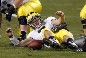 Photo - Michigan's Shane Morris fumbles the ball, which he later recovered, during the second half of the Buffalo Wild Wings Bowl NCAA college football game against Kansas State, Saturday, Dec. 28, 2013, in Tempe, Ariz. Kansas State defeated Michigan 31-14. (AP Photo/Ross D. Franklin)