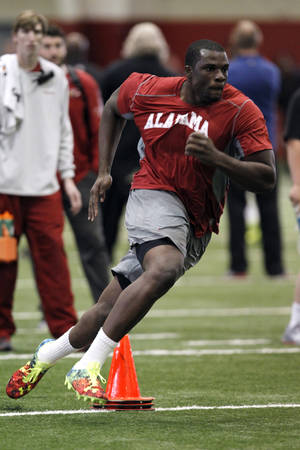 Photo - Cyrus Kouandjio runs drills for NFL scouts during Pro Day at the University of Alabama on Wednesday, Mar. 12, 2014, in Tuscaloosa, Ala. (AP Photo/Butch Dill)