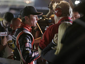 Photo - Driver Kurt Busch sips on a drink as he talks to the media after dropping out of the NASCAR Sprint Cup series Coca-Cola 600 auto race at Charlotte Motor Speedway in Concord, N.C., Sunday, May 25, 2014. (AP Photo/Chuck Burton)