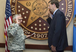 Photo -                    Maj. Gen. Myles Deering, Oklahoma's adjutant general, administers the oath of enlistment to Dr. Brian Levy, 59, of Edmond, during an informal ceremony at the Oklahoma National Guard's Joint Force Headquarters in Oklahoma City.                                       photo provided by                                                          Army Sgt. 1st Class                                                          Kendall James