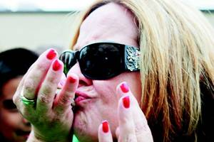 Photo - Jacklyn Mercer kisses a frog Tuesday at Mark Twain Elementary as part of the school's annual frog races. (Duncan Banner photo)