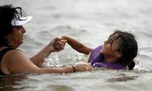 Photo - Louise Medina swims with her granddaughter Gabrielia  Ortiz, 4, at a beach in Lake Arcadia, Friday, July 2, 2010, in Edmond, Okla. Photo by  Sarah Phipps, The Oklahoman