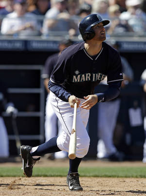Photo - Seattle Mariners' Brad Miller hits a triple during the third inning of a spring exhibition baseball game against the Milwaukee Brewers, Wednesday, March 19, 2014, in Peoria, Ariz. (AP Photo/Darron Cummings)