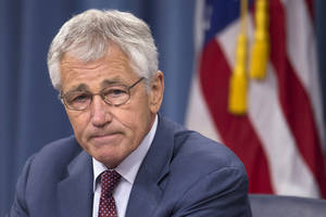 Photo - Defense Secretary Chuck Hagel pauses during a news conference at the Pentagon, Wednesday, July 31, 2013. Hagel warned that the Pentagon may have to mothball up to three Navy aircraft carriers and order more sharp reductions in the size of the Army and Marine Corps if Congress does not act to avoid massive budget cuts beginning in 2014.  (AP Photo/Evan Vucci)
