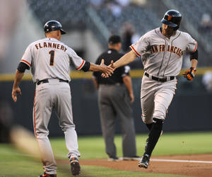 Photo - San Francisco Giants' Hunter Pence, right, is congratulated by third base coach Tim Flannery after hitting a two-run home run off Colorado Rockies starting pitcher Chad Bettis during the first inning of a baseball game on Tuesday, Aug. 27, 2013, in Denver. (AP Photo/Jack Dempsey)