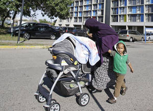 Photo - In this photo taken Tuesday, Sept. 24, 2013, a young Somali boy accompanies  his mother who covers her head to avoid being photographed by the high rise where many Somali people live in Minneapolis. It's been six years since Minnesota first began furnishing young fighters to al-Shabab, the terror group that has claimed responsibility for the deadly mall attack in Kenya. (AP Photo/Jim Mone)