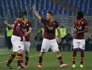 Photo - AS Roma's Francesco Totti, center, celebrates with teammates after scoring during a Serie A soccer match between AS Roma and Udinese in Rome's Olympic stadium, Monday, March 17, 2014. (AP Photo/Gregorio Borgia)