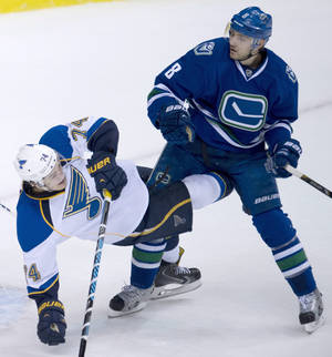 Photo - Vancouver Canucks defenseman Chris Tanev (8) fights for control of the puck with St. Louis Blues right wing T.J. Oshie (74) during the second period of an NHL hockey game Friday, Jan. 10, 2014, in Vancouver, British Columbia. (AP Photo/The Canadian Press, Jonathan Hayward)