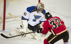 Photo - St. Louis Blues goalie Jaroslav Halak, left, from Slovakia, blocks a shot from Calgary Flames' Paul Byron during first-period NHL hockey game action against the Calgary Flames in Calgary, Alberta, Thursday, Jan. 9, 2014. (AP Photo/The Canadian Press, Jeff McIntosh)