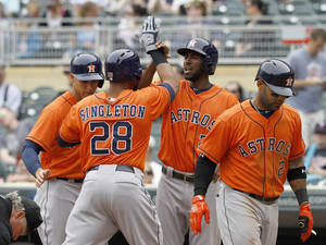 Photo - Houston Astros'  Jon Singleton (28) is congratulated by teammates George Springer, left, Dexter Fowler and Jonathan Villar, right, after Singleton's grand slam off Minnesota Twins relief pitcher Glen Perkins during the ninth inning of a baseball game in Minneapolis, Sunday, June 8, 2014. The Astros won 14-5. (AP Photo/Ann Heisenfelt)